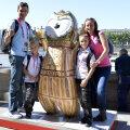 Eduard şi Laura Novak alături de copii, de mascota aurie cu un fundal caracteristic Londrei