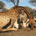 Stoicikov zâmbește lângă girafa doborâtă la safari