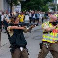 Polițiștii țintesc cu armele automate, în timp ce oamenii trec speriați prin spatele lor // FOTO Guliver/GettyImages