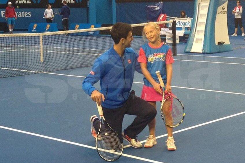 Novak Djokovici şi micuţa jucătoare Anna Bishop în prim-plan, iar în spatele lor, în stînga, se află Simona Halep alături de antrenorii ei