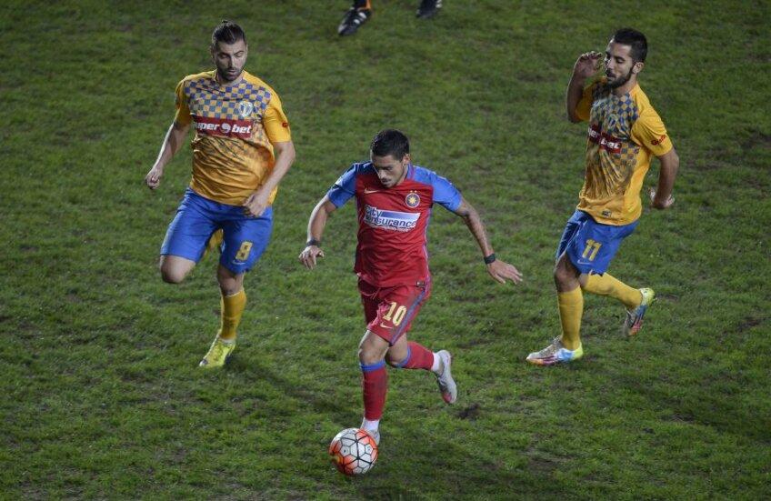 Stanciu, urmărit de Ropotan şi Velasco, încearcă să controleze mingea pe un gazon impracticabil