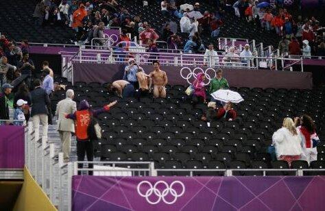 Hei, voi ce faceţi aici? Toată lumea rîde de striperii de ocazie, mai puţin un steward (stînga, cu vesta Jocurilor Olimpice), care gesticulează nervos spre cei trei curajoşi Foto: Reuters