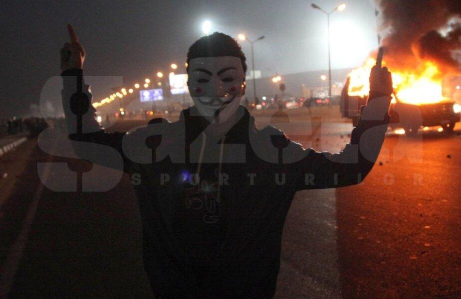 Isterie la Cairo. Un fan mascat în faţa unei maşini de poliţie în flăcări