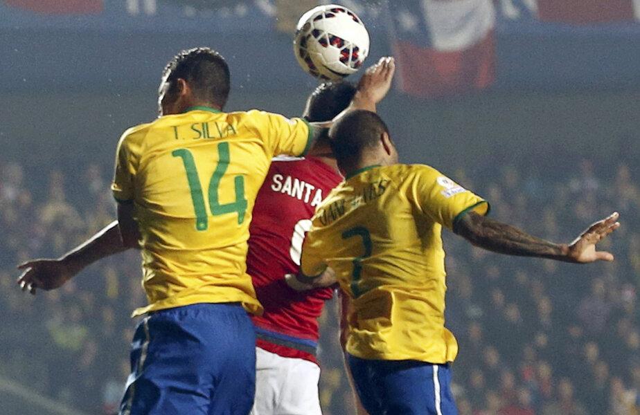 Thiago Silva (nr. 14) sare peste Dani Alves și blochează mingea cu mîna deasupra lui Santa Cruz // Foto: Reuters