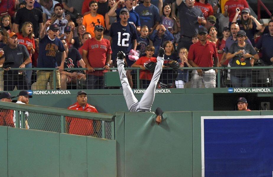 NOW YOU SEE ME... Austin Jackson (Cleveland Indians) cade peste zid în încercarea de a prinde mingea lovită de Hanley Ramirez (Boston Red Sox). Priviți expresiile de pe fețele celor din tribună. :) foto: Reuters