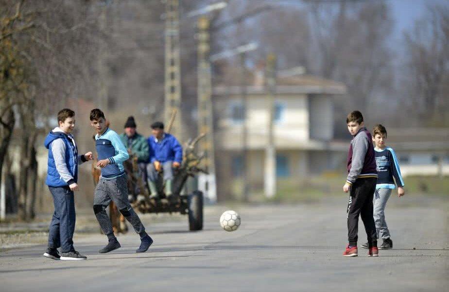 Copiii se joacă fotbal pe ulițele satului Traian