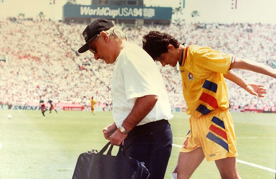 Pompiliu Popescu, pe marginea terenului, cu Belodedici, la meciul cu SUA de la CM 1994, când fundașul s-a ales cu un genunchi paradit în timpul jocului